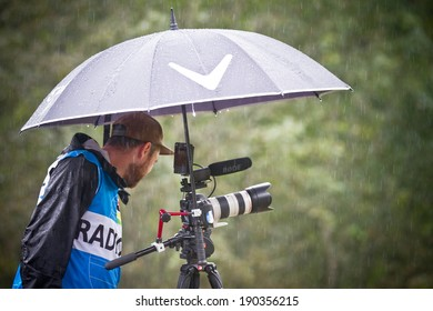 CHAMPERY, SWITZERLAND, SEPTEMBER 21: An unidentified photographer as he stands under an umbrella to protect his gear against the rain during the UCI downhill world championships 2011.