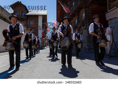 CHAMPERY, VALAIS/SWITZERLAND - AUGUST 1: Traditional bell ringers demonstrating their art of bellringing during swiss national day celebrations in Champery, Valais, Switzerland, august 1st 2013.