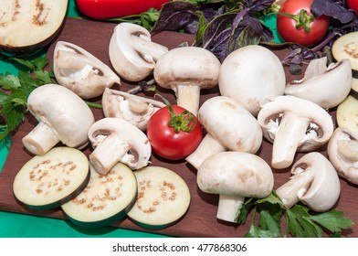 Champignon and fresh vegetables on a kitchen table for cooking dishes from mushrooms