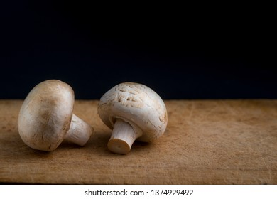 champignon mushrooms on a wooden board on a black background