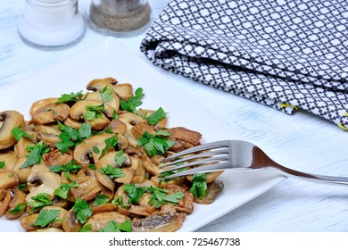 Champignon in a plate with parsley on table