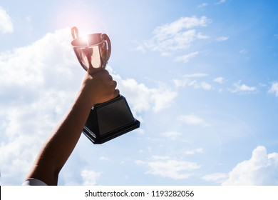 Champion Asian Student holding up silver trophy cup with blue sky shiny background, copy space for text success award  for studying or sport in school.