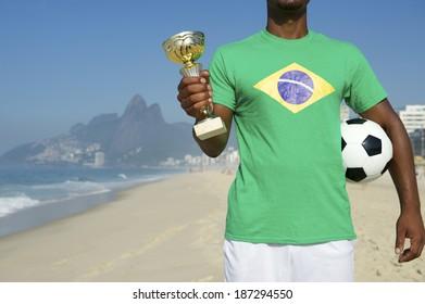 Champion Brazilian soccer player holding trophy and football in Brazilian flag shirt Ipanema Beach Rio de Janeiro Brazil