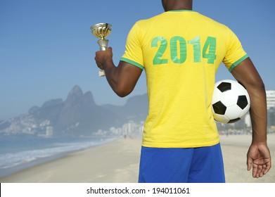 Champion Brazilian soccer player holding trophy and football in 2014 shirt Ipanema Beach Rio de Janeiro Brazil