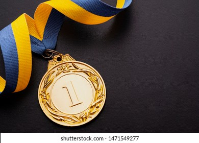 Champion or first placed winner gold medallion with twirled gold and blue ribbon over a dark grey background with copy space viewed from overhead