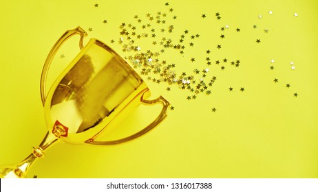 Champion gold cup trophy on yellow background. minimalism style, victory celebration concept. and golden stars of confetti are scattered around