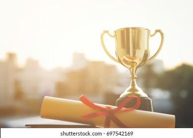 Champion golden trophy with Graduation certificate on city sunset time with copy space. Success and Education concept.
