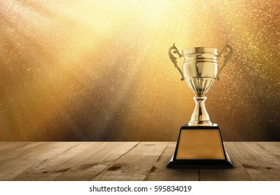 champion golden trophy on wood table with copy space and gold Twinkly Lights and glitter stars light background copy space ready for your design.