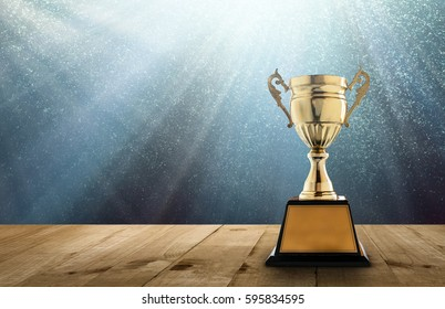 champion golden trophy on wood table with copy space and blue Twinkly Lights and glitter stars light background copy space ready for your design.