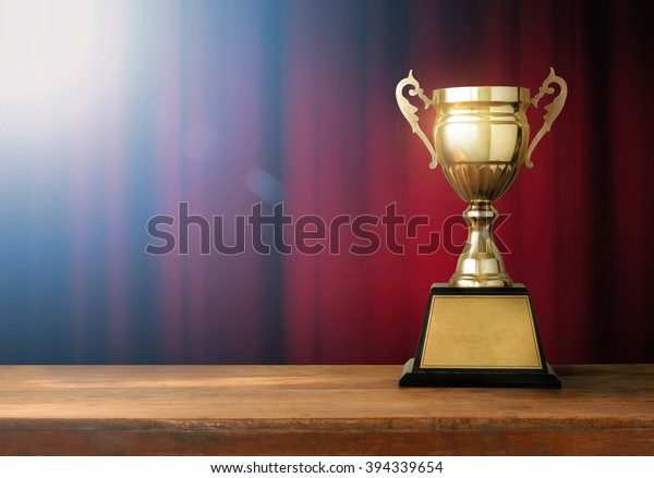 champion golden trophy on wood table with spot light and Red closed curtain background