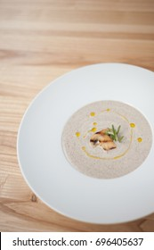 Champion mushrooms cream soup in white plate on wooden background