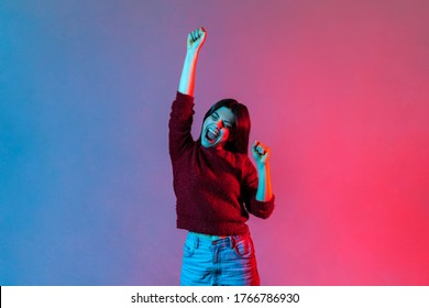 I am champion! Neon light portrait of victorious delighted happy brunette woman raising hands, shouting for joy, screaming celebrating win success, thrilled emotions. indoor studio shot isolated