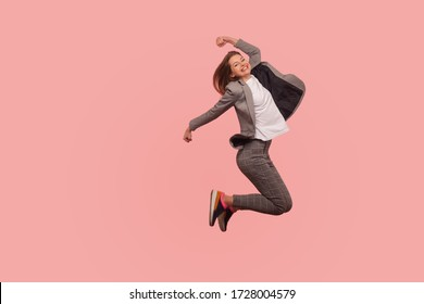 I'm champion! Portrait of enthusiastic ecstatic happy businesswoman in elegant suit jumping carefree in air, flying inspired by success, celebrating goal achievement. indoor studio shot isolated