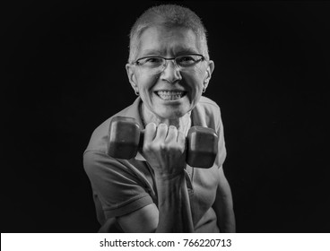 Champion senior lady, lifting weights using dumbbells and feeling strong and powerful; dramatic atmosphere
