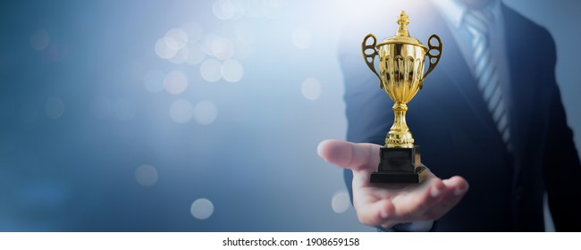 Champion and success winner concept, businessman holding cup of leadership trophy and champ of business on soft blue and bokeh background