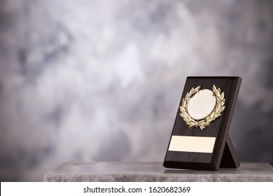 champion  trophy plaque placed on marble table with gray background copy space ready for your winning design concept.