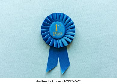 Champion or Winners 1st Place blue rosette with gold text placed in the center on a light blue background with copy space