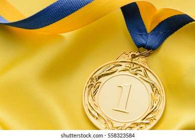 Champions first place gold medal on a twirled ribbon to be awarded to the winner of a competition or sporting event on gold cloth with copy space