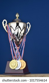 A championship and victory trophy on blue background with gold, silver, bronze medals