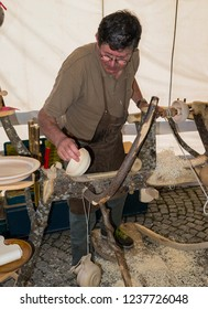 Champoluc, Aosta Valley, Italy - August 10, 2018: Craftsman using a self-built wood lathe during a local fair.