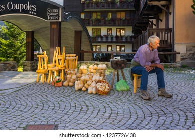 "Champoluc, Aosta Valley, Italy - August 10, 2018: Craftsman selling wooden objects and the traditional hooves used in Valle d'Aosta and called ""sabot""."