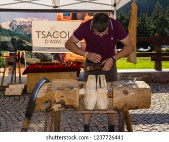 "Champoluc, Aosta Valley, Italy - August 10, 2018: Craftsman manufacturing the traditional clogs used in Aosta Valley and called ""sabot"", during a local fair."