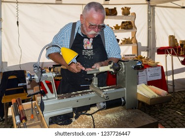 Champoluc, Aosta Valley, Italy - August 10, 2018: Craftsman using a modern wood lathe during a local fair.