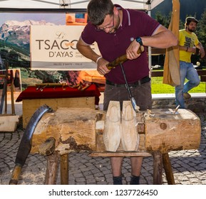 "Champoluc, Aosta Valley, Italy - August 10, 2018: Craftsman manufacturing the traditional clogs used in Aosta Valley and called ""sabot"", during a local fair, and a man with a glass in the background."