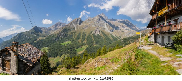 Champoluc, Aosta Valley, Italy - August 24, 2011: Mountain house with roof shingles and a stone chimney pot, and a mountain refuge on the right (Ayas Valley, Aosta Valley, Italy).
