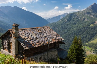 Champoluc, Aosta Valley, Italy - August 24, 2011: Mountain house with roof shingles and a stone chimney pot (Ayas Valley, Aosta Valley, Italy).