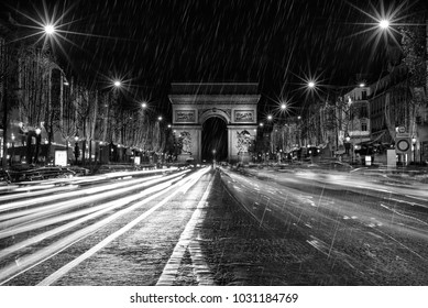 champs elysee illuminated at night while it rains - photography converted to black and white