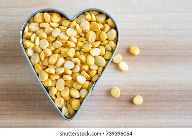 Chana Dal yellow lentils. Concept of healthy eating. The legume is inside a heart shape on a wooden surface.
