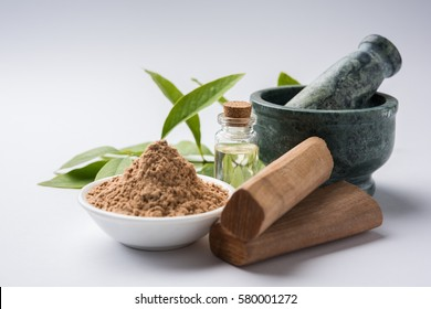 Chandan or sandalwood powder with sticks, traditional mortar, perfume or oil in miniature bottle and green leaves. selective focus