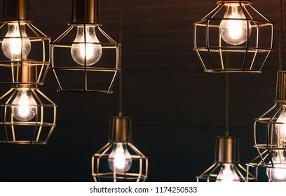 Chandelier with hanging bulb lamps, yellow LED lighting elements covered with metal wire frame lampshades, photo with selective focus