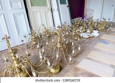 Chandelier lights antique gold on floor salvage removed from ceiling in construction site