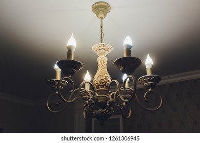 Chandelier on ceiling with classic design decorations and lights on in six lamps.