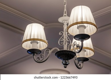 A chandelier with three electric lamps and lampshades hanging on the ceiling. Concept cozy evening in the hotel, theater during intermission