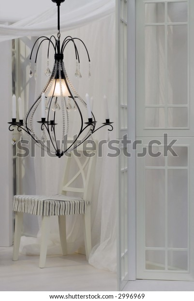 chandelier in white interior with chair, curtain and windows