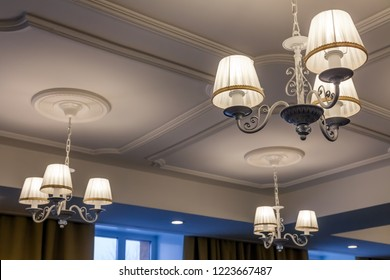 Chandeliers with three electric lamps and lampshades hanging on the ceiling. Concept cozy evening in the hotel, theater during intermission