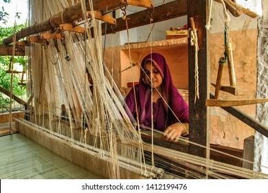 Chanderi, Madhya Pradesh, India - October 14, 2017 : A women weaver at work making a sari in Chanderi, a famous sari producing town in Chanderi, Madhya Pradesh, India.