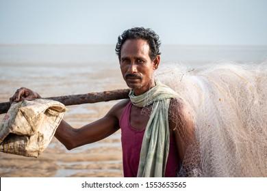 Chandipur beach, Balasore, Odisha, India - April 9, 2019: Fisherman going for fishing in the Indian Ocean carrying a net