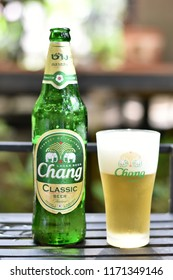 """""""Chang Classic"""" beer in green bottle and glass with logo on blurred bokeh background.Chang is a brand of Thai beverage is Thailand's largest beverage companies.Sep 3,2018 : Chiang Mai, Thailand."""