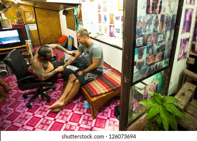 CHANG, THAILAND - JAN 27: Unidentified master makes traditional tattoo bamboo, Jan 27, 2012 in Chang, Thailand. Thai tattooists are very popular among tourists, prices range from 500 thai baht and up.