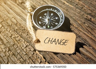 CHANGE inscription written on paper tag, compass on old wooden background