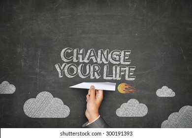 Change your life concept on black blackboard with businessman hand holding paper plane