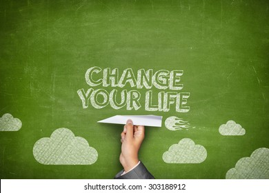 Change your life concept on green blackboard with businessman hand holding paper plane