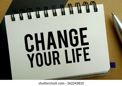 Change your life memo written on a notebook with pen