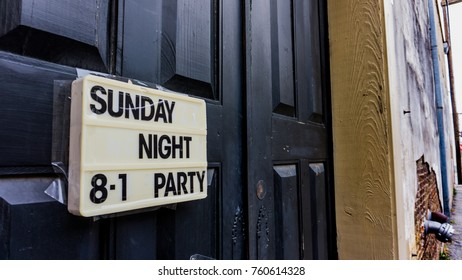 Changeable sign on a door in a back alleyway advertising a party