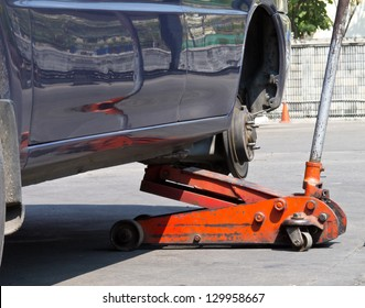 Changing car tire with hand jack