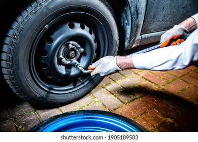 Changing a car tyre, tire. Unscrewing lug nuts on the wheel with a lug wrench, selective focus.